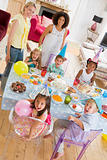Young children at party with mothers sitting at table with food