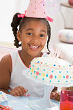 Young girl wearing party hat with cake in front of her smiling