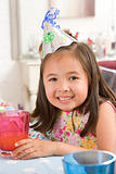Young girl wearing party hat at table smiling