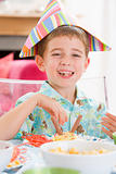 Young boy at party sitting at table with food smiling