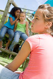 Two young girl friends at a playground whispering about other gi