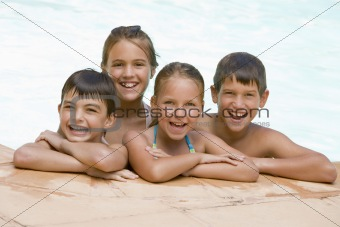 Four young friends in swimming pool smiling