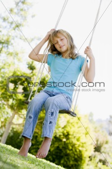 Young girl sitting on swing smiling