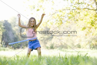 Young girl with hula hoop outdoors smiling