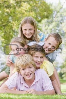 Five young friends piled on each other outdoors smiling