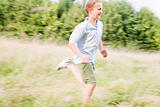 Young boy running in a field smiling