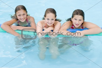 Three young girl friends in swimming pool with pool noodle smili