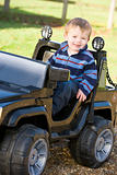Young boy playing outdoors in toy truck smiling
