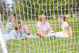 Five young friends on soccer field talking and smiling