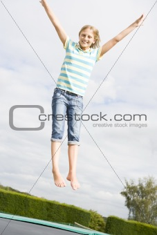 Young girl jumping on trampoline smiling