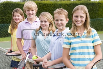 Five young friends with rackets on tennis court smiling