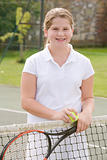 Young girl with racket on tennis court smiling