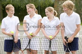 Four young friends with rackets on tennis court smiling