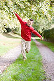 Young boy running on a path outdoors smiling