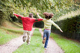 Two young friends running on a path outdoors
