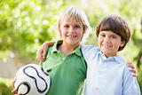 Two young boys outdoors with soccer ball smiling