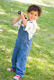 Young boy holding baseball bat outdoors smiling