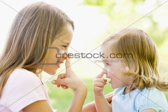 Two sisters playing outdoors and smiling