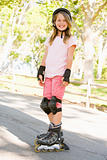 Young girl outdoors on inline skates smiling