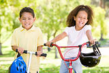 Brother and sister outdoors with scooter and bicycle smiling