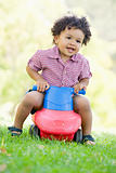 Young boy playing on toy with wheels outdoors