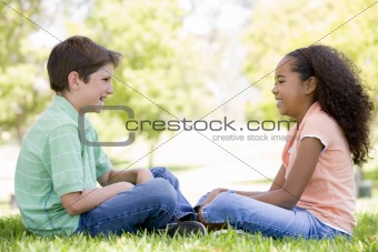 Tow young friends sitting outdoors looking at each other and smi