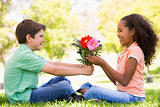 Young boy giving young girl flowers and smiling