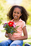 Young girl holding flowers and smiling