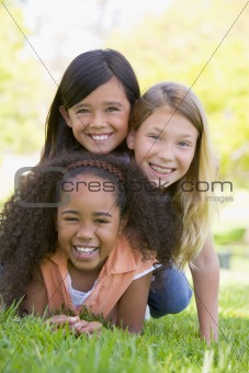 Three young girl friends piled up on top of each other outdoors