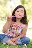 Young girl blowing bubbles outdoors