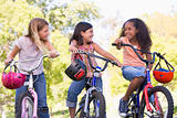 Three young girl friends outdoors on bicycles smiling