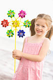 Young girl at beach with toy windmill smiling