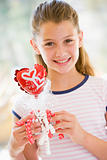 Young girl on Valentine's Day holding love themed balloon smilin