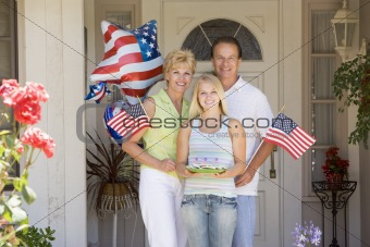Family at front door on fourth of July with flags and cookies sm
