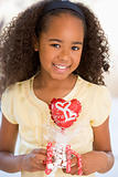 Young girl on Valentine&#39;s Day holding love themed balloon smilin