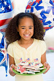 Young girl on fourth of July with balloons and cookies smiling