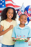 Brother and sister on fourth of July with flag and cookies smili