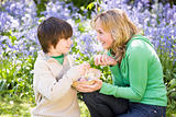 Mother and son on Easter looking for eggs outdoors smiling