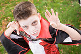 Young boy outdoors wearing vampire costume on Halloween