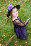 Young girl outdoors in witch costume on Halloween