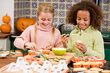 Two young girl friends at Halloween making treats and smiling
