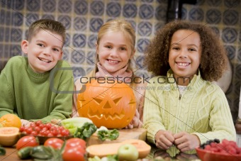 Three young friends on Halloween with jack o lantern and food sm