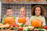 Three young friends on Halloween with jack o lanterns and food s