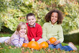 Three young friends sitting on grass with pumpkins smiling
