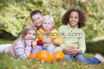 Three young friends with baby sitting on grass with pumpkins smi