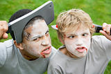 Two young boys with scary Halloween make up and plastic knives t