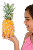 Young girl holding pineapple and smiling