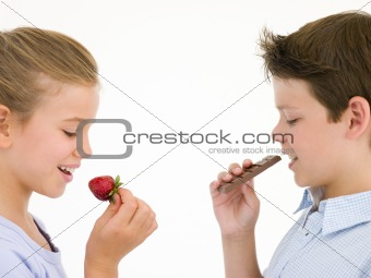 Sister eating strawberry by brother eating chocolate bar