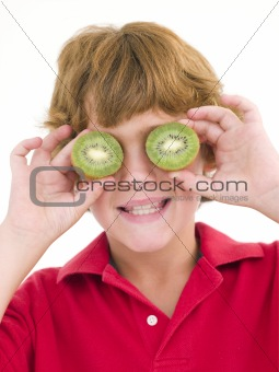 Young boy holding kiwi halves over eyes smiling