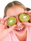Young girl holding kiwi halves over eyes smiling